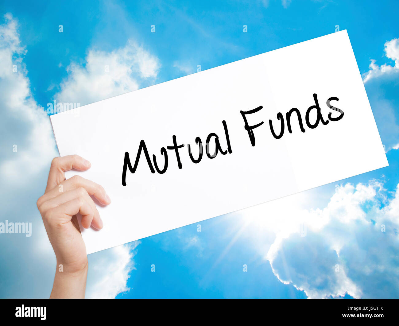 Mutual Funds  Sign on white paper. Man Hand Holding Paper with text. Isolated on sky background.   Business concept. - Stock Image
