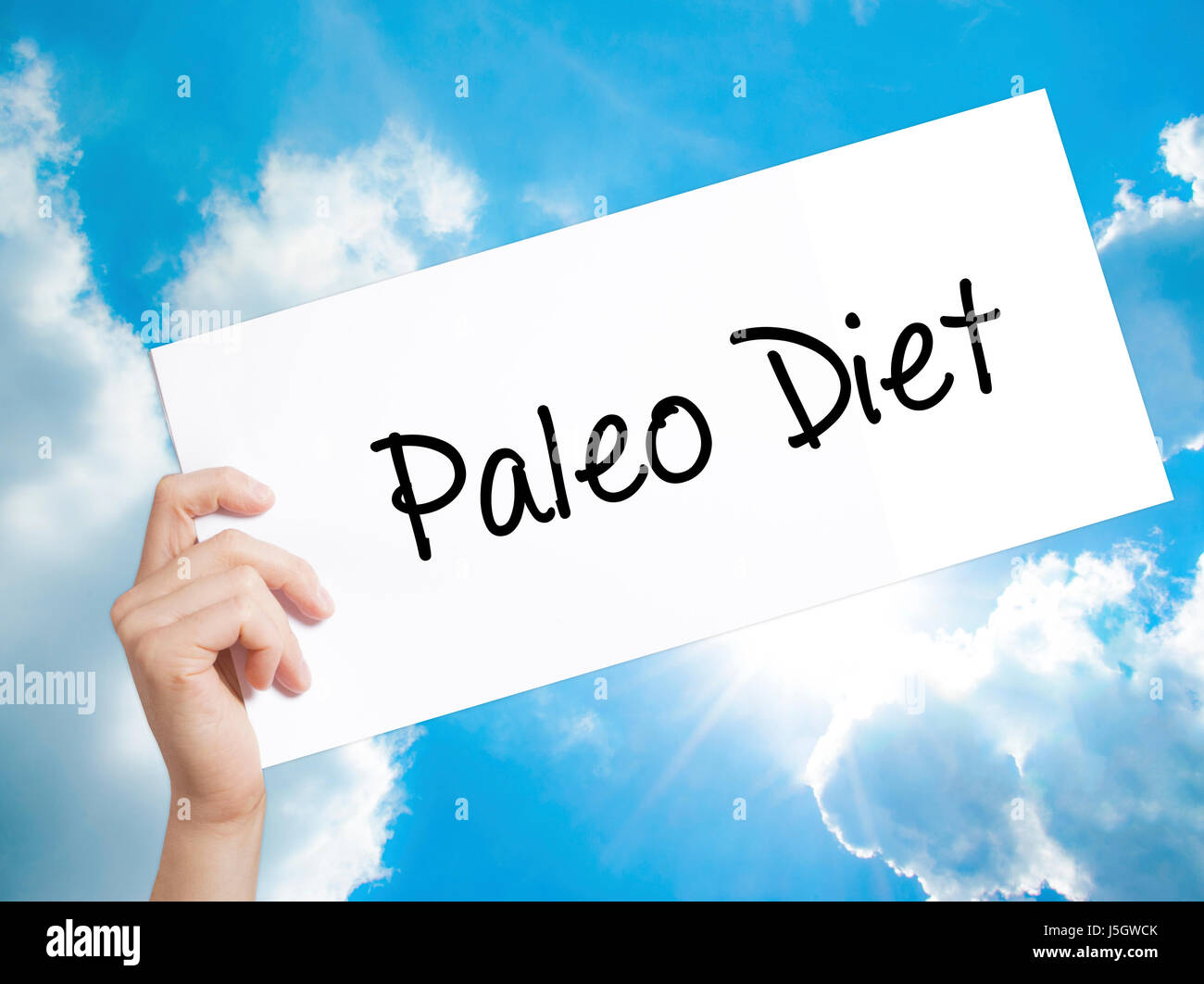 Paleo Diet Sign on white paper. Man Hand Holding Paper with text. Isolated on sky background.   Business concept. - Stock Image
