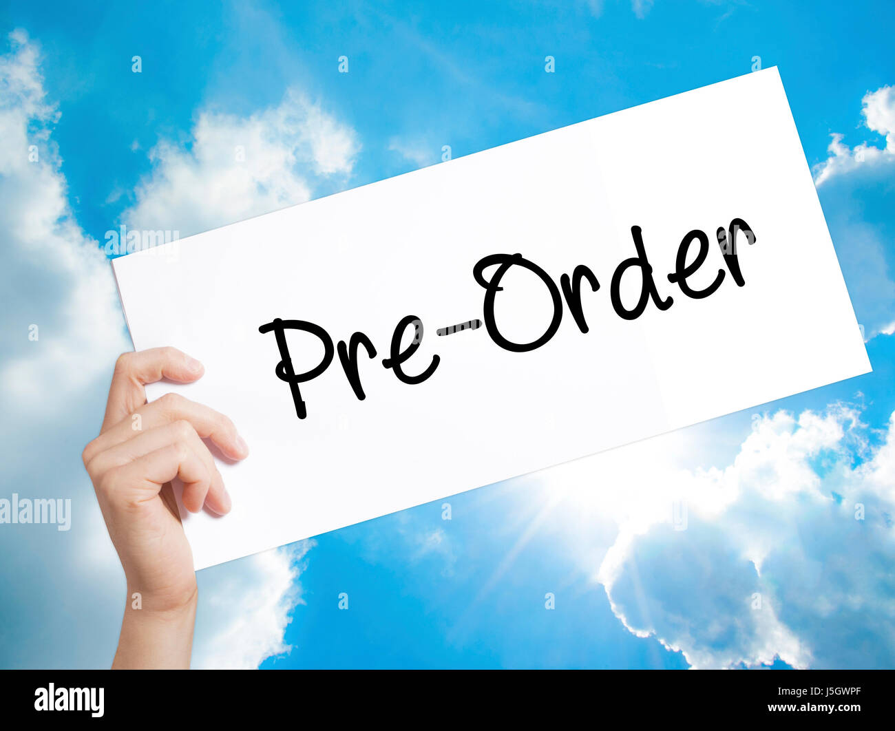 Pre-Order  Sign on white paper. Man Hand Holding Paper with text. Isolated on sky background.  Business concept. - Stock Image