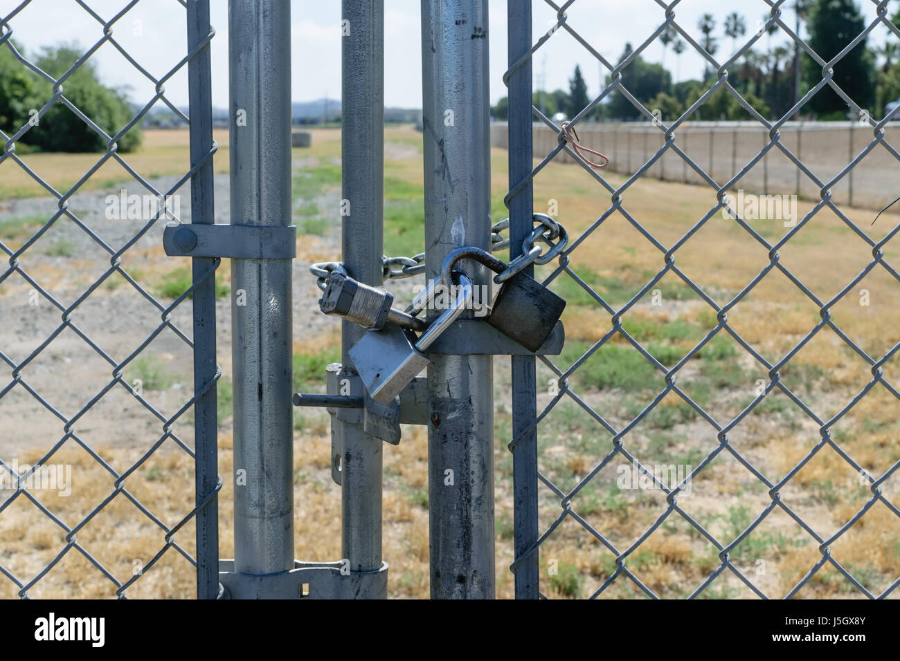 Three locks secure gate on fence - Stock Image