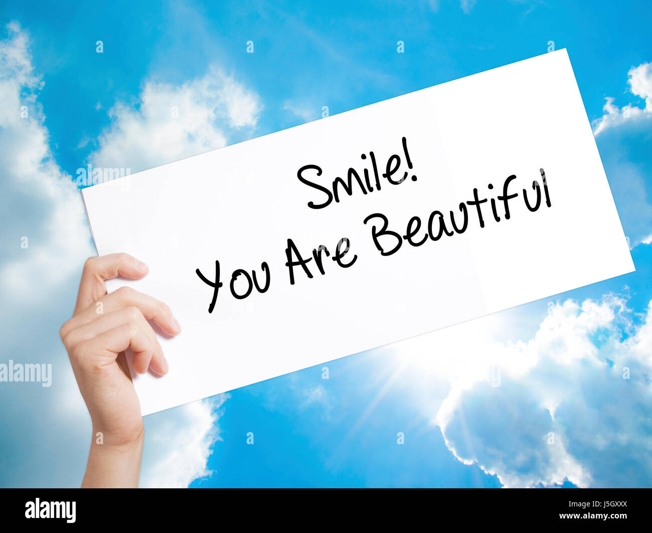 Smile! You Are Beautiful Sign on white paper. Man Hand Holding Paper with text. Isolated on sky background.  Business Stock Photo