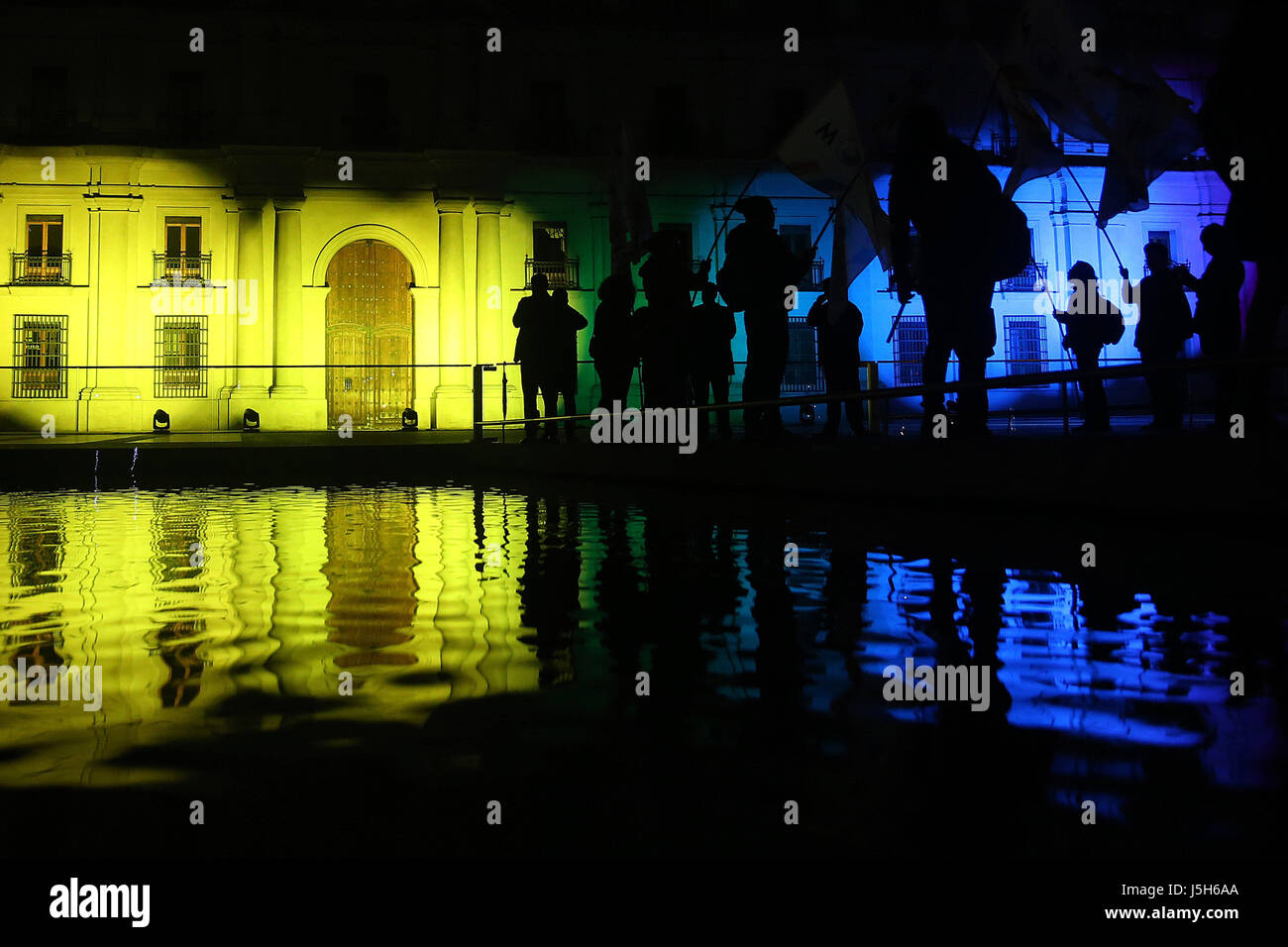 People observe the facade of La Moneda Palace illuminated with the colors of the rainbow flag in Santiago, Chile, - Stock Image