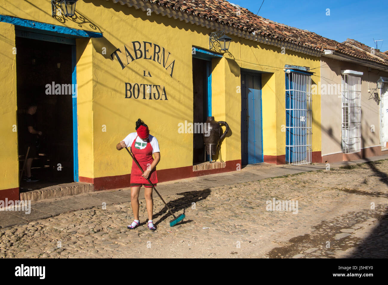 Woman in Trinidad Cuba sweeping cobblestone street outside a tavern - Stock Image