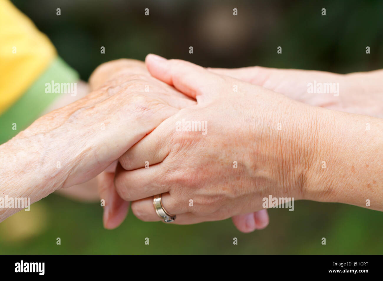 Caregiver touching and holds an elderly wrinkled hand - Stock Image