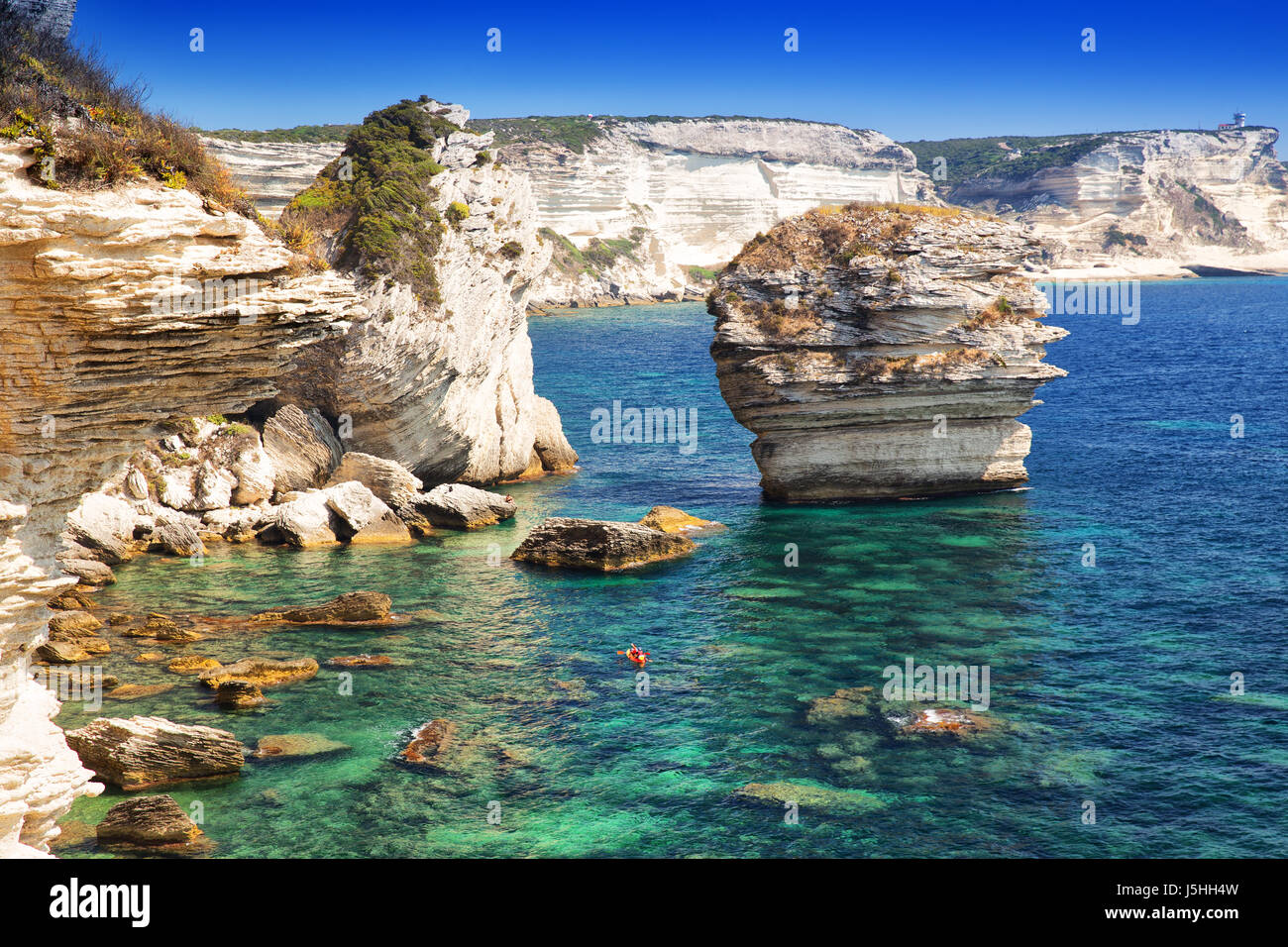 Young couple kayaking near Bonifacio town on beautiful white rock cliff with sea bay, Corsica, France, Europe. - Stock Image