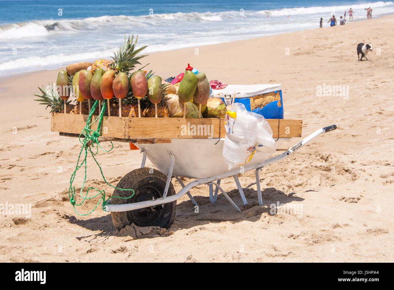 A wheelbarrow uniquely and crudely designed to serve fruit and fruit drinks at a beach, beautiful beach, people - Stock Image