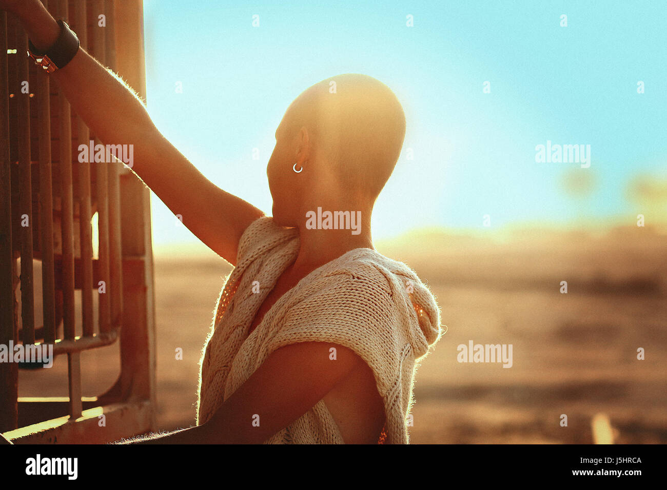 Shaved-headed girl silhouette on the sunset scenery, desert view with blue sky and sands,old vintage trains and - Stock Image