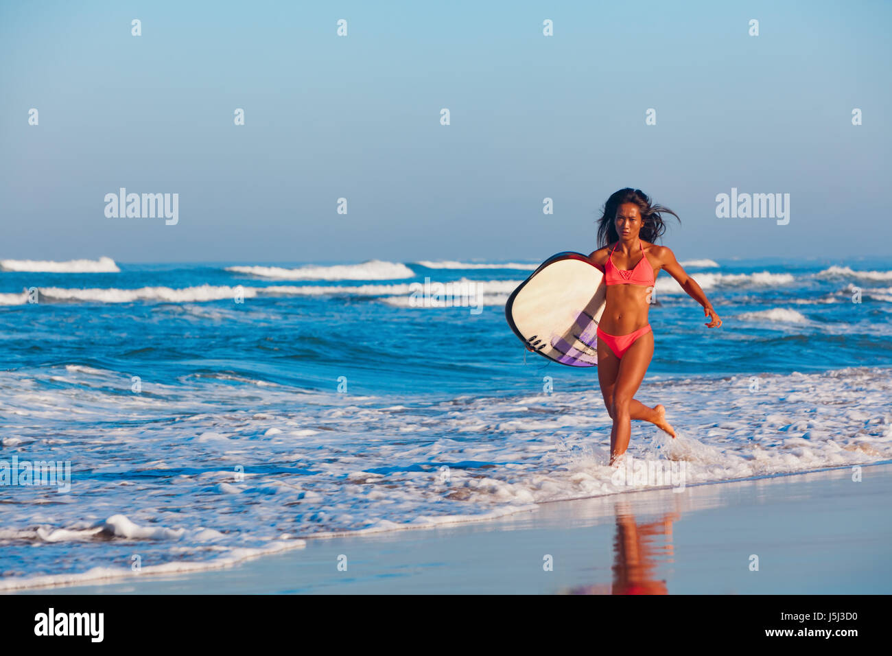 Girl in bikini with surf board has fun. Woman surfer run into water, jump with splashes through ocean wave. People - Stock Image