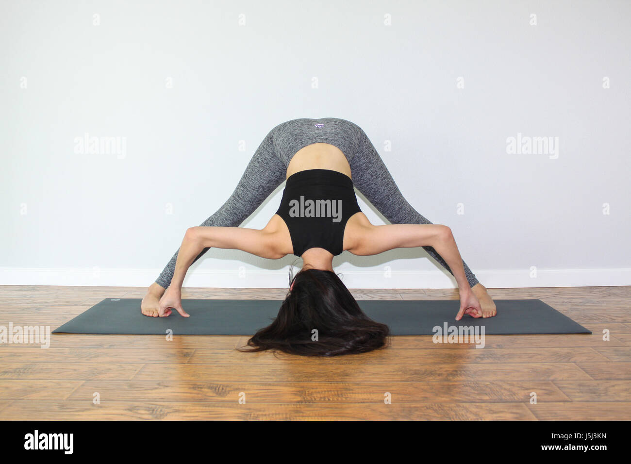 Beautiful woman doing a yoga pose called, wide-legged standing forward fold. - Stock Image