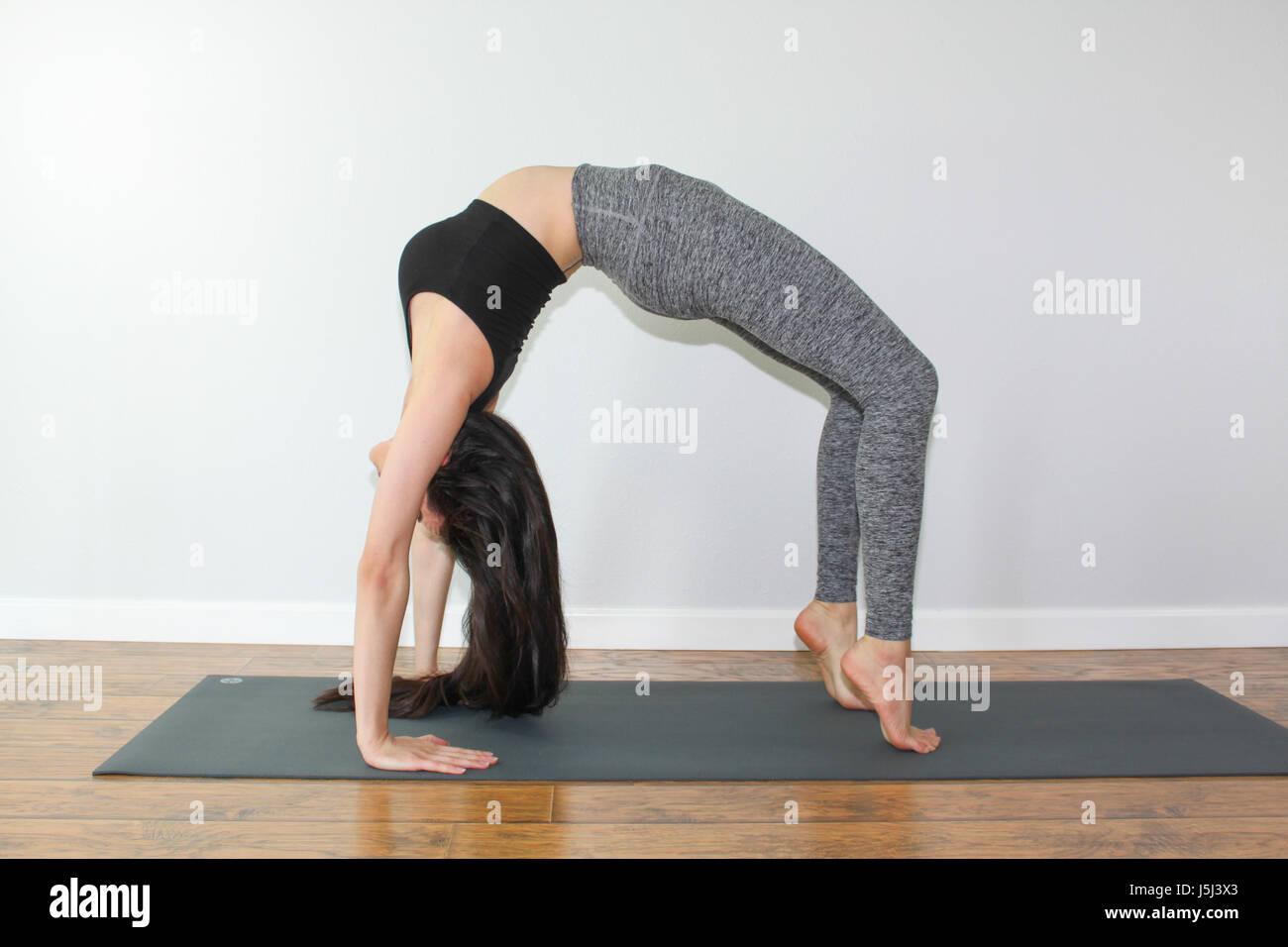 Beautiful woman doing a yoga pose called wheel pose. - Stock Image