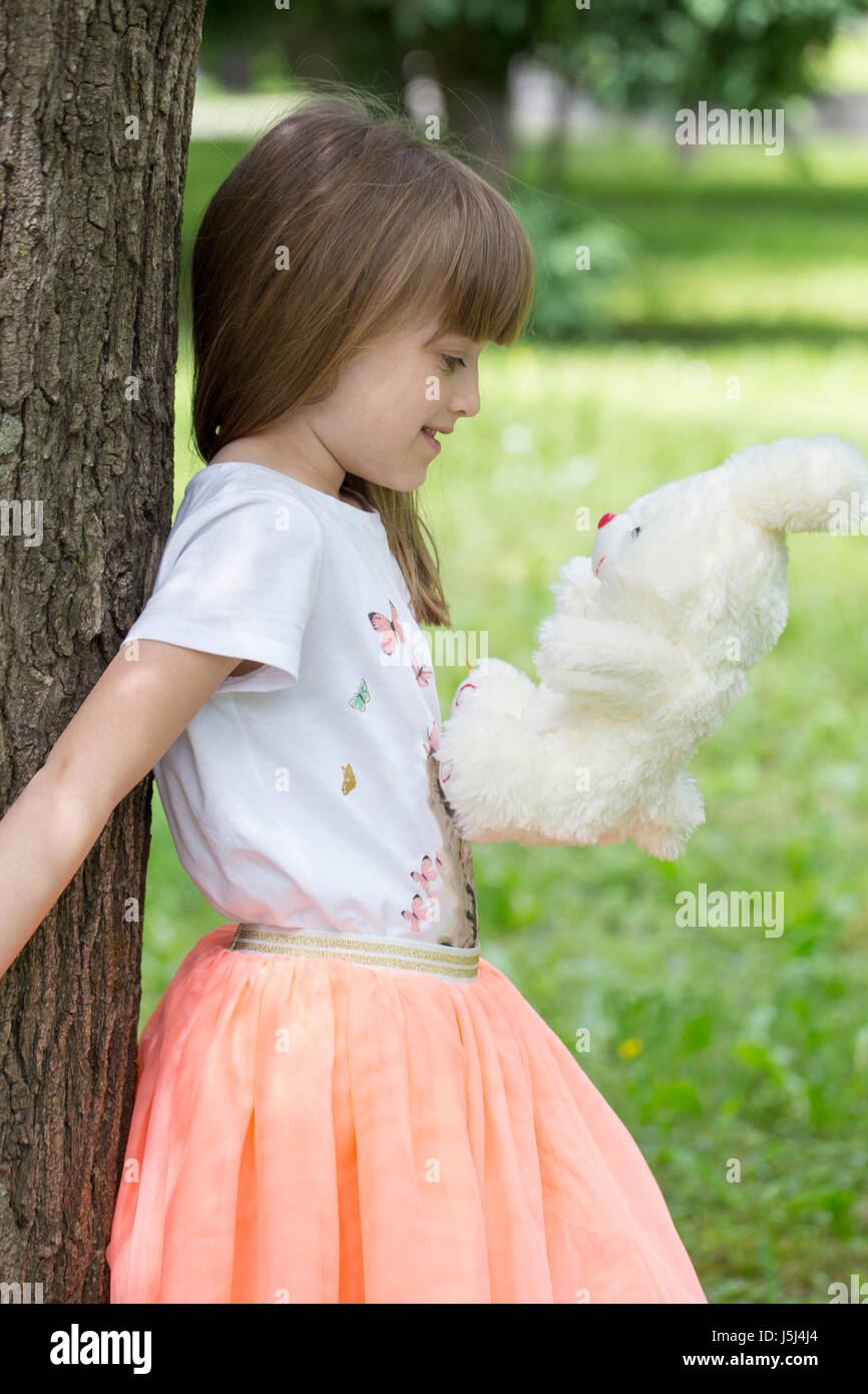 The little girl leaning against a tree holding her favorite stuffed toy Stock Photo