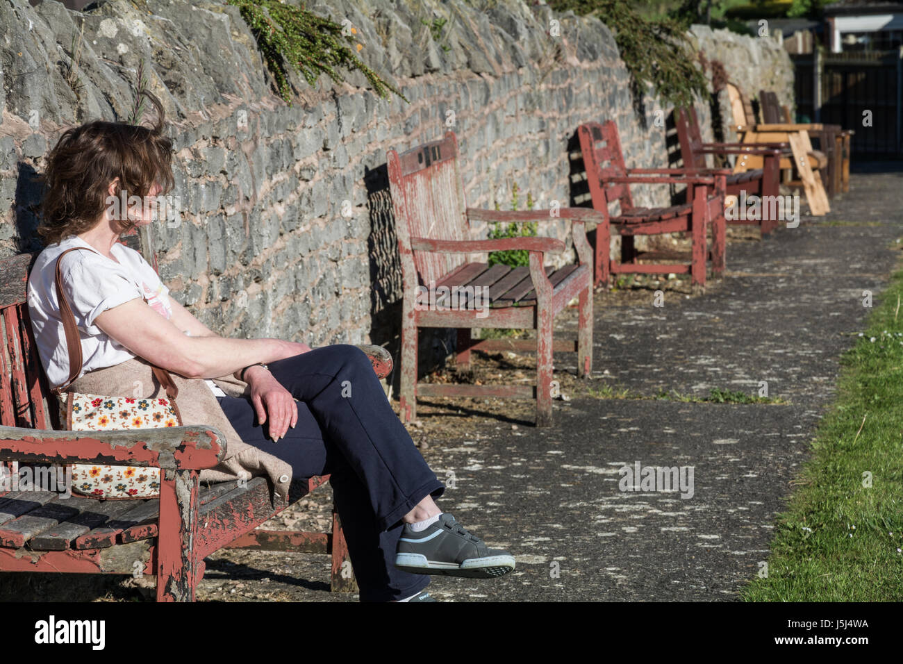 Middle aged woman sitting on a bench relaxing on a breezy, sunny day. Shropshire, UK, Summer. - Stock Image
