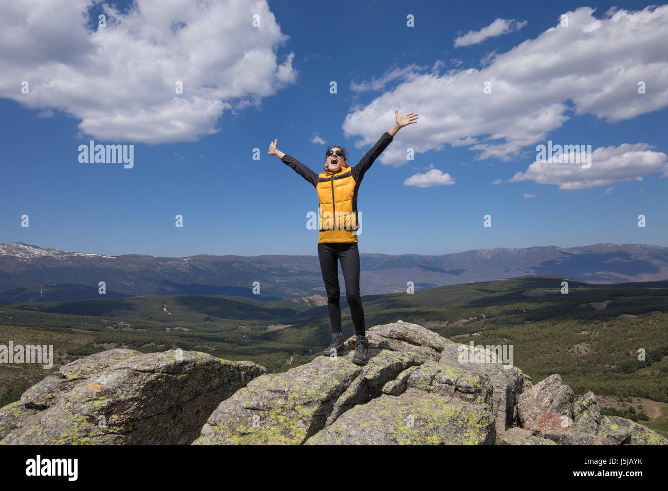 sport hiking or trekking woman with yellow jacket, standing on rock peak, with arms up and screaming open mouth, - Stock Image