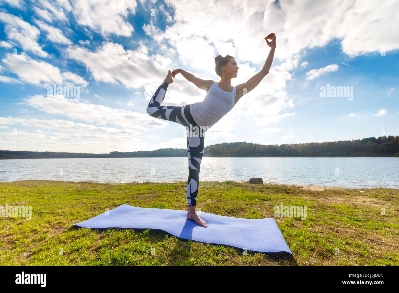 Young Woman Doing Yoga Near Lake Outdoors Meditation Sport Fitness And Exercising In Nature Autumn Sunset