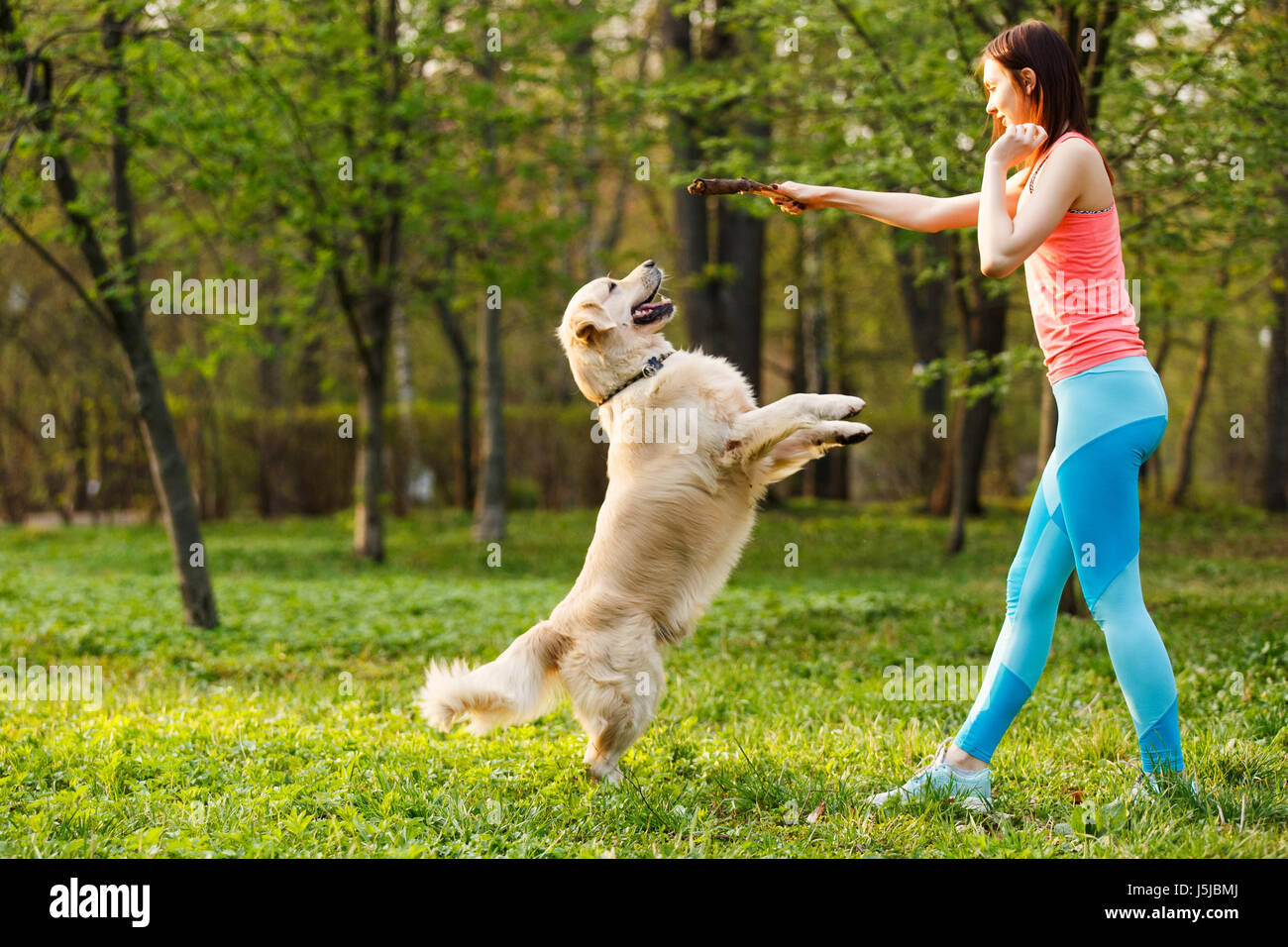 Sporty woman playing with dog - Stock Image