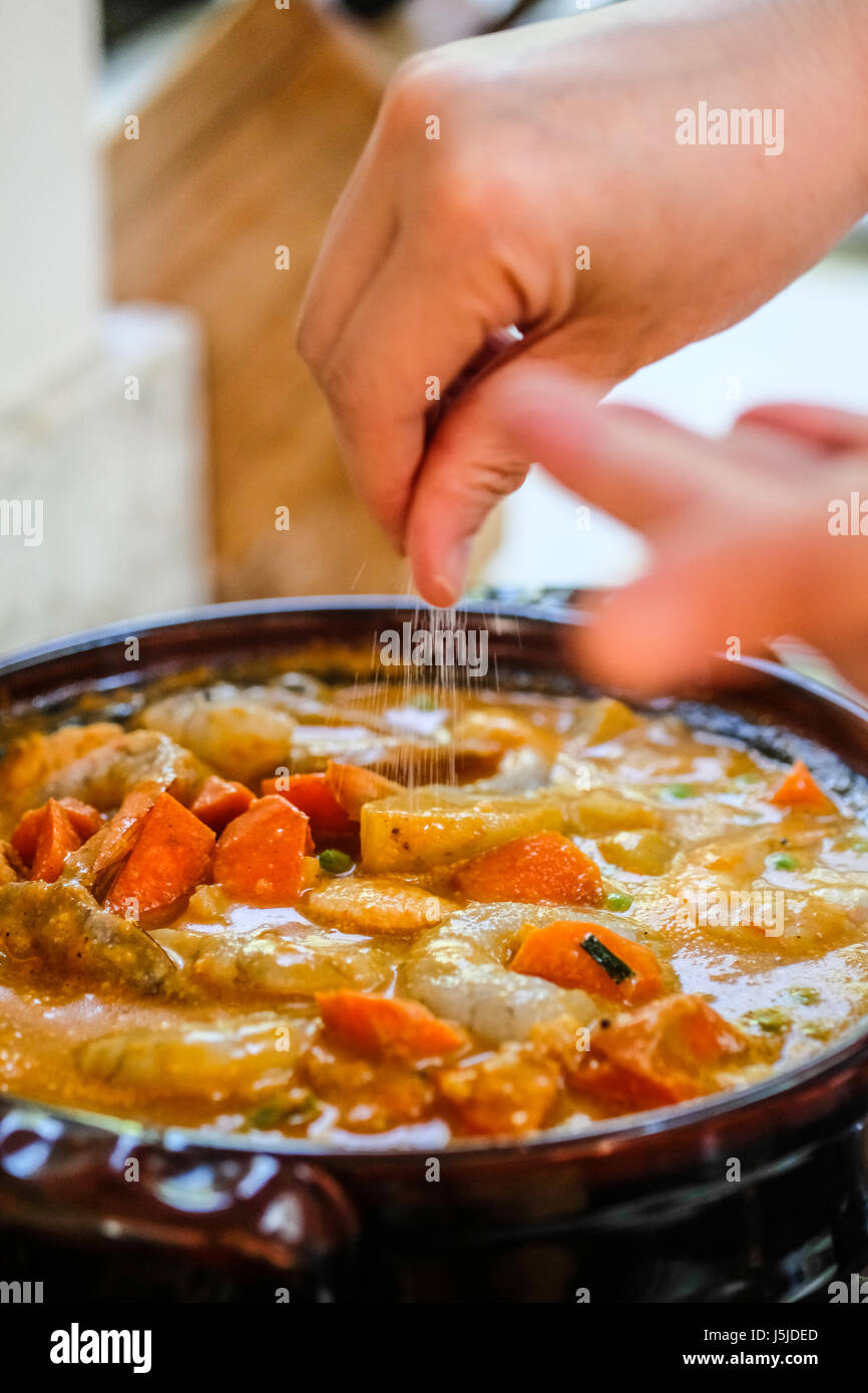 A vertical image of female hands sprinkling salt over a pot of seafoods on the stove - Stock Image