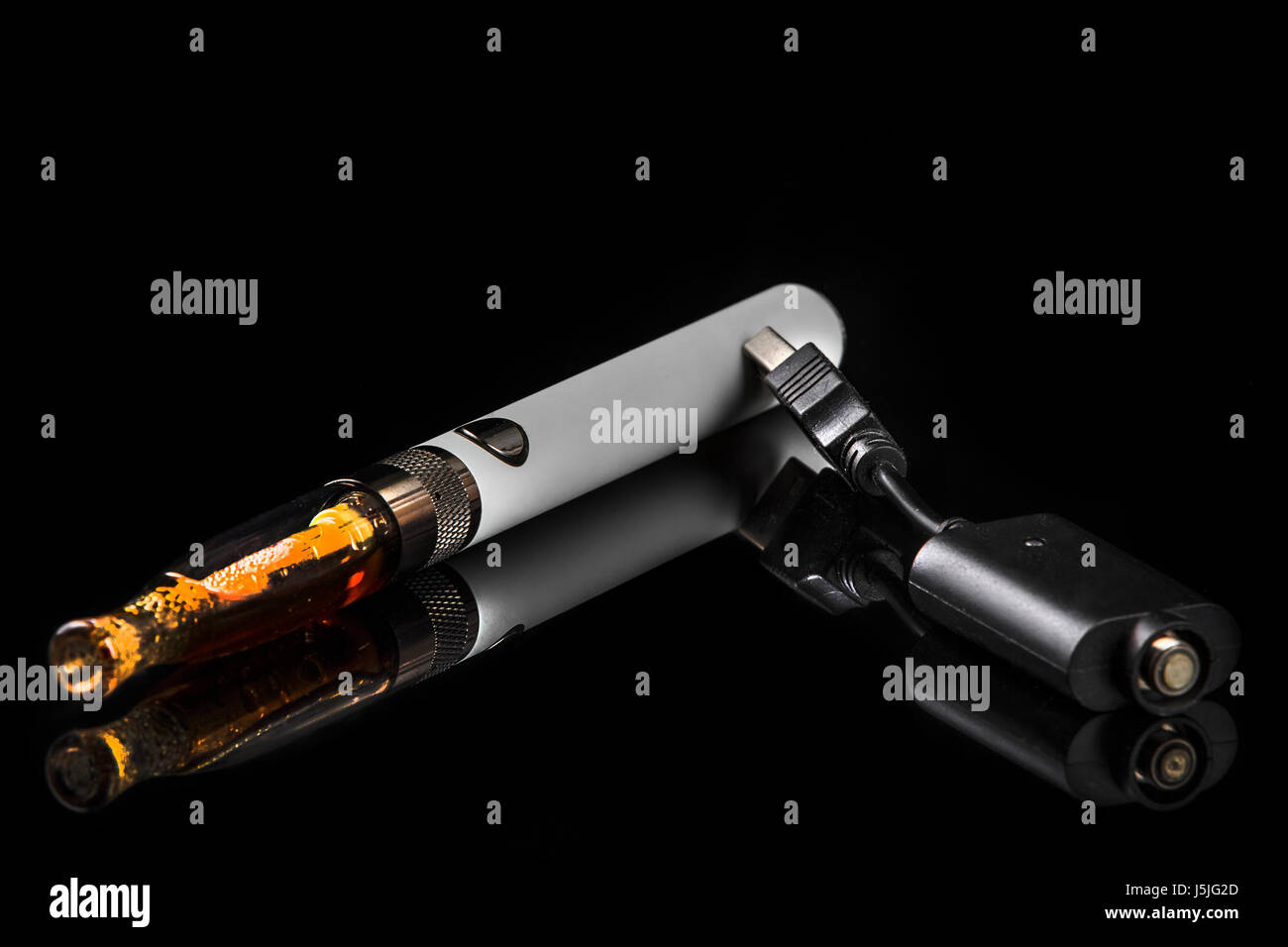 Electronic cigarette with charger on a black background. - Stock Image