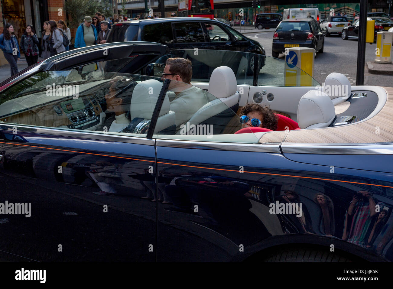 Wealthy adults and a child wearing sunglasses who smiles in the back of an open-top car remaining stationary at - Stock Image