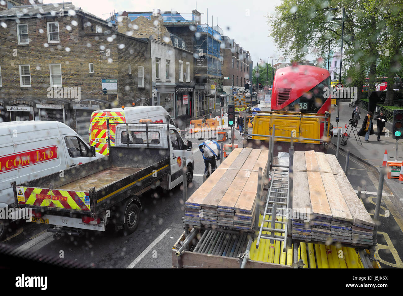 Cyclist cycling between construction lorries behind double-decker bus in heavy traffic on Essex Road near Islington - Stock Image