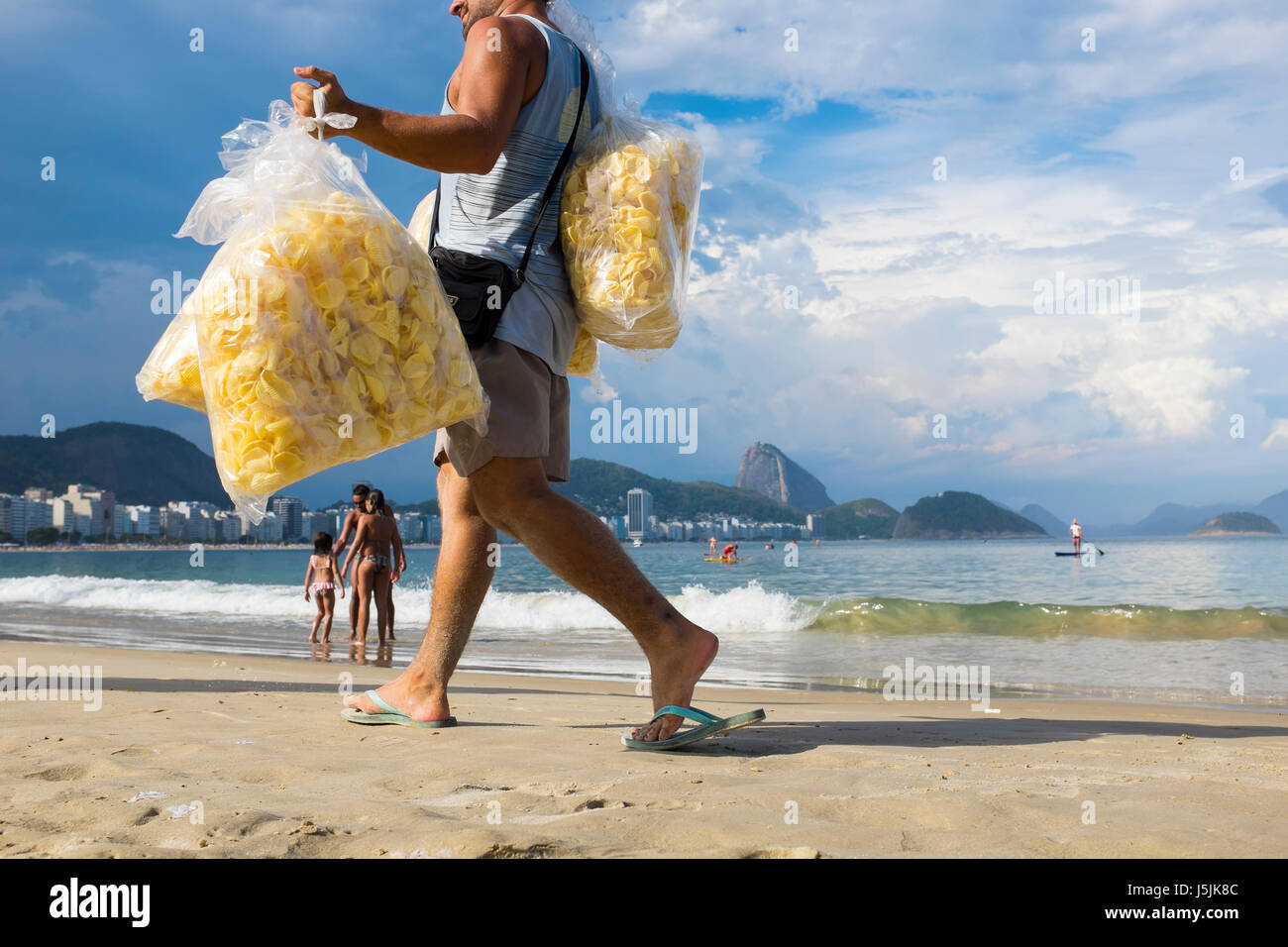 RIO DE JANEIRO - MARCH 2, 2017: A Brazilian vendor walks along Copacabana Beach carrying bags of potato chips for - Stock Image