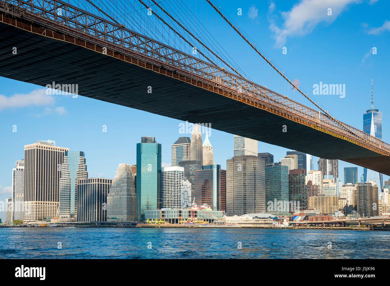 Bright scenic view of the Brooklyn Bridge with the Lower Manhattan skyline from the East River - Stock Image
