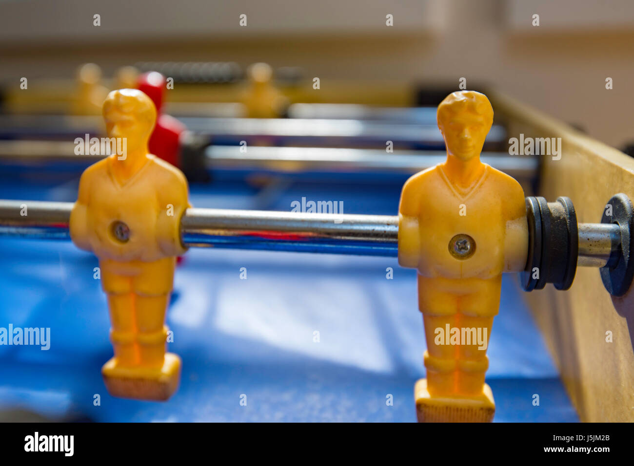 An old fussball, foosball or table football game which has painted white and red players - Stock Image