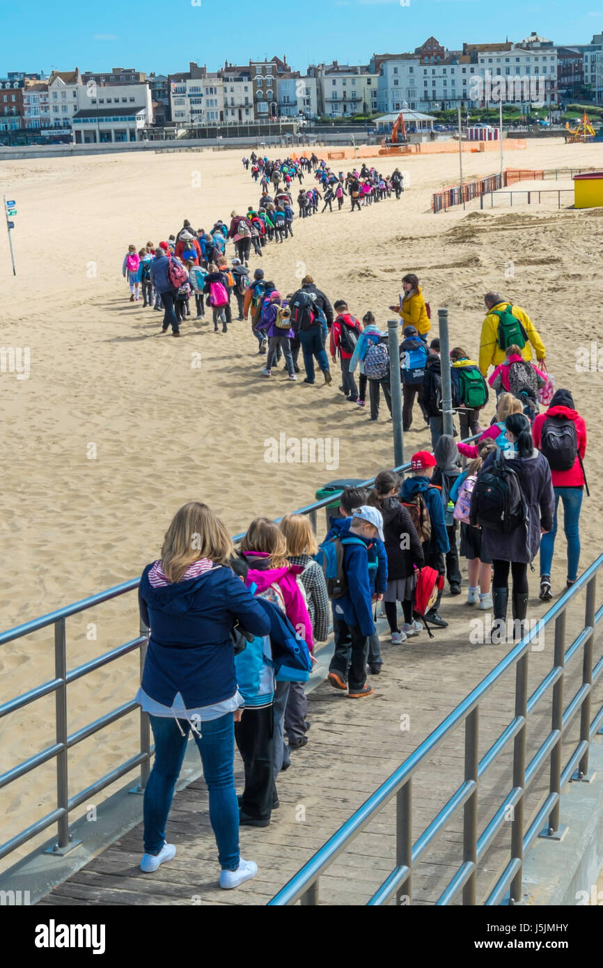 A long line of young school children with their teachers and helpers on a daytrip walking across the beach at Margate, - Stock Image