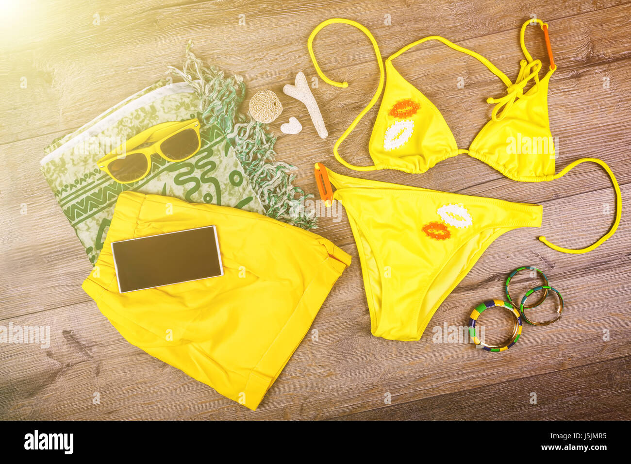 Set of beach clothes yellow bikini, bracelets, shorts, glasses on dark wooden background. Top view. Summer Holiday - Stock Image