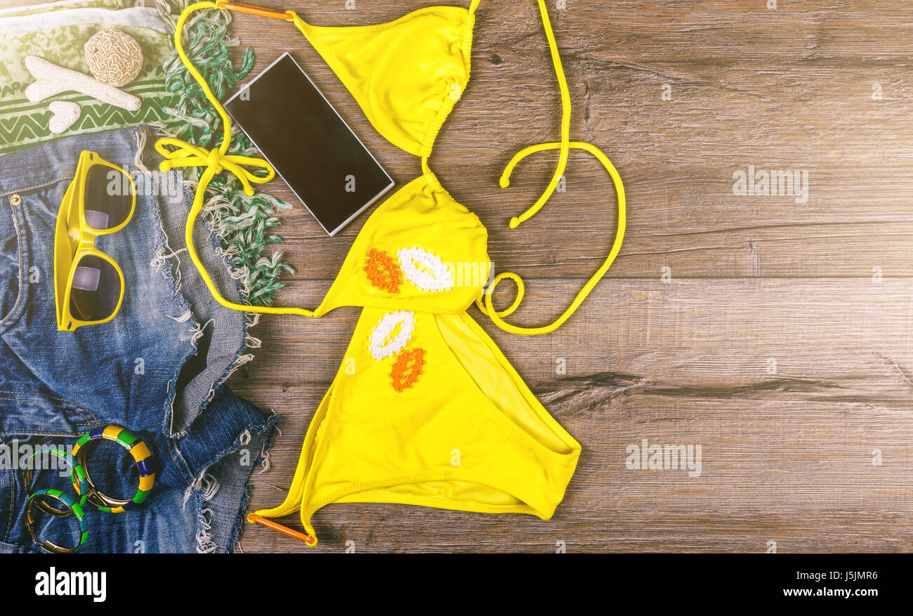 Set of beach clothes yellow bikini, bracelets, jeans shorts, glasses on dark wooden background. Top view. Summer - Stock Image