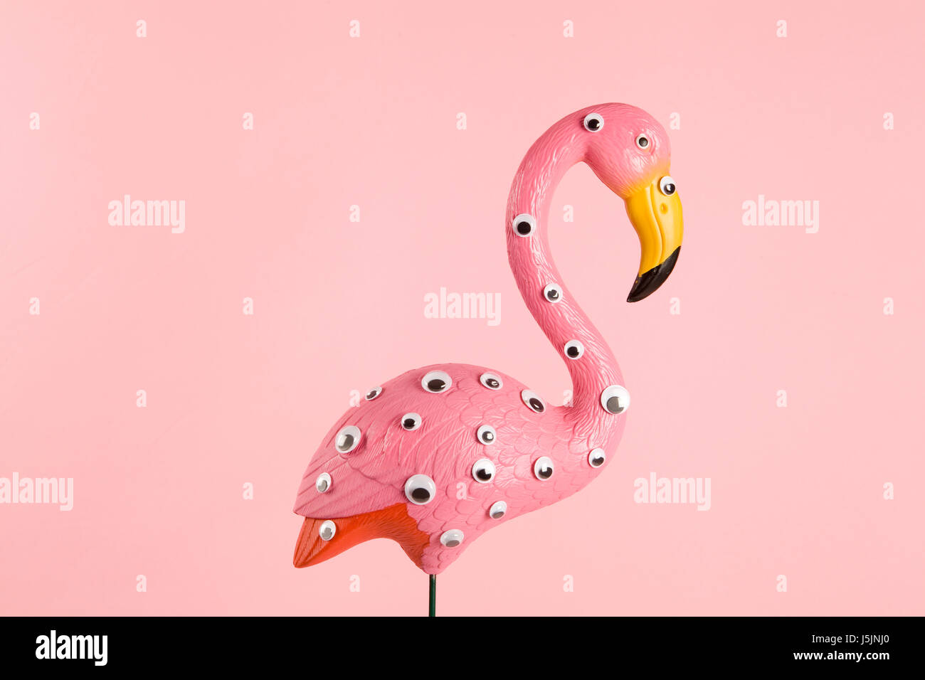 quirky and freak pink plastic flamingo on a pink background with numerous eyes gradient and tones on tones - Stock Image