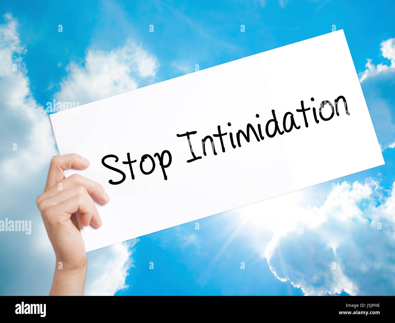 Stop Intimidation Sign on white paper. Man Hand Holding Paper with text. Isolated on sky background.  Business concept. - Stock Image