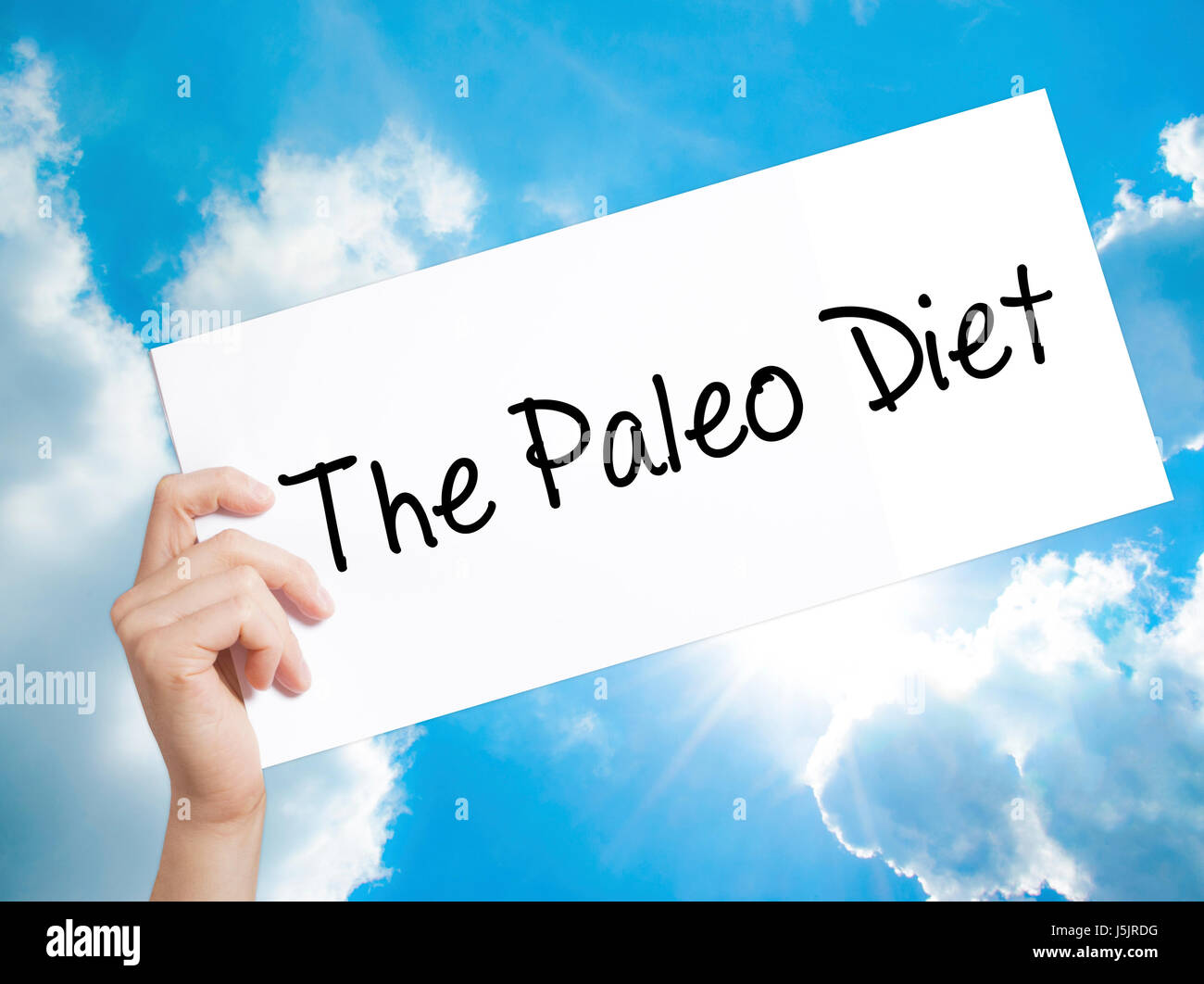 The Paleo Diet Sign on white paper. Man Hand Holding Paper with text. Isolated on sky background. Medical, Business - Stock Image