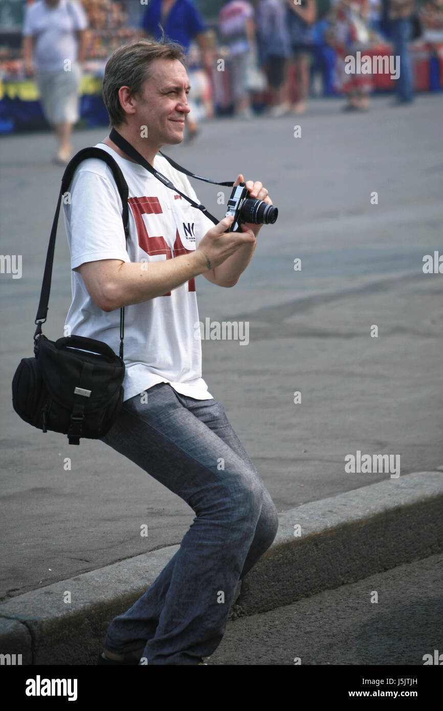 The young man with a camera in hands in a dynamical pose in the street - Stock Image