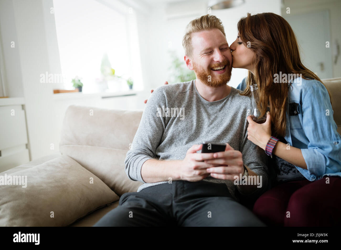 Romantic young couple expressing their love by kissing - Stock Image
