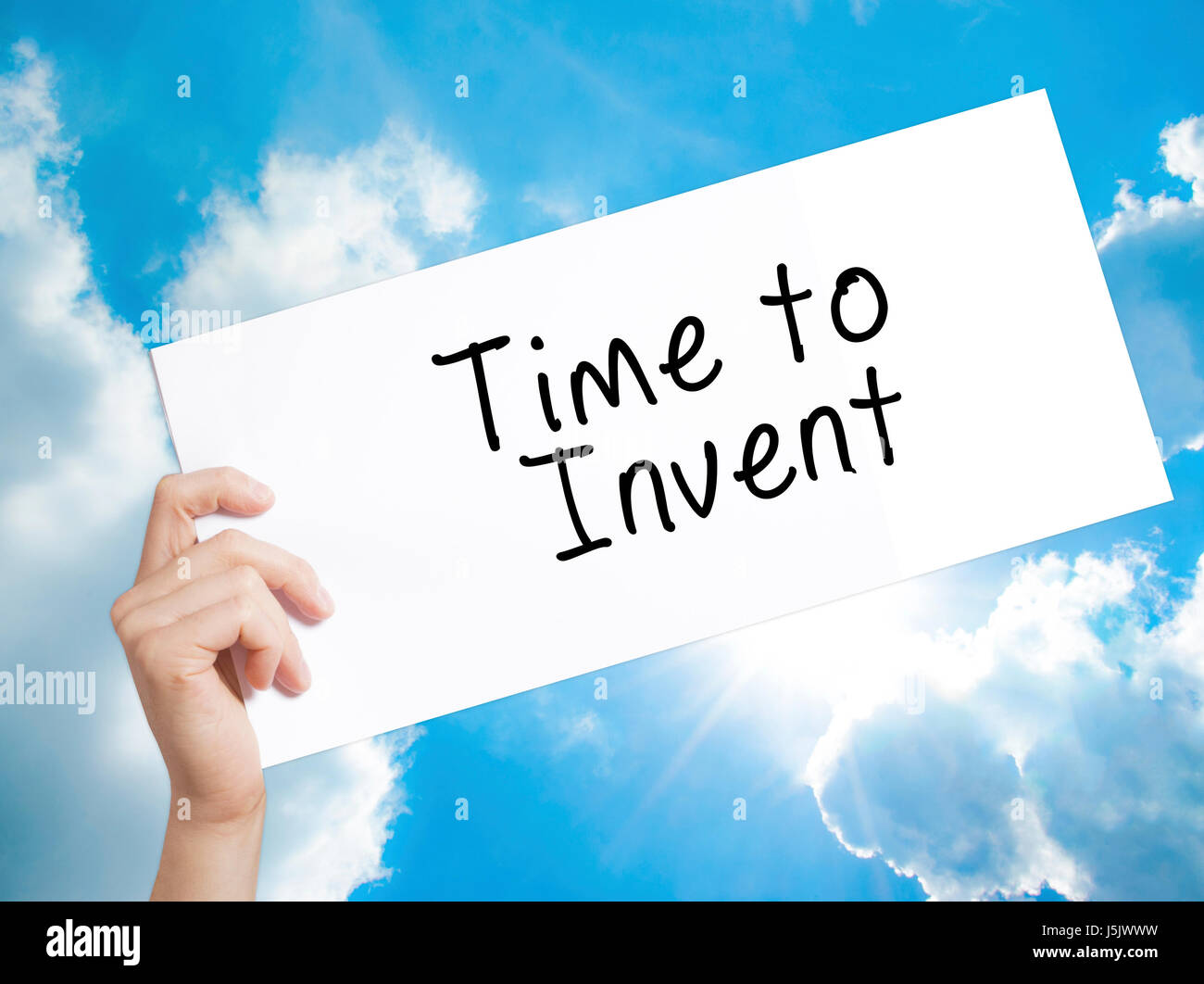 Time to Invent Sign on white paper. Man Hand Holding Paper with text. Isolated on sky background.  Business concept. - Stock Image