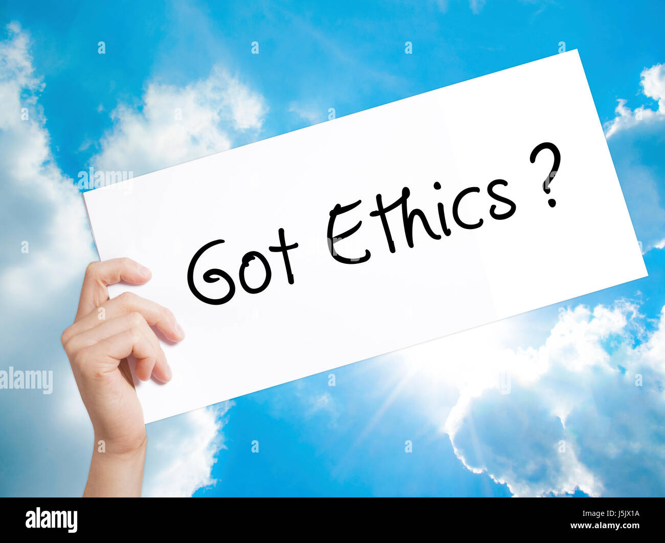 Got Ethics Sign on white paper. Man Hand Holding Paper with text. Isolated on sky background.  Business concept. - Stock Image