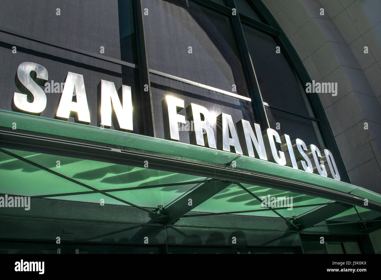 Sunlit San Francisco sign above Ferry entrance to embarkation boat piers on Embarcadero San Francisco California - Stock Image