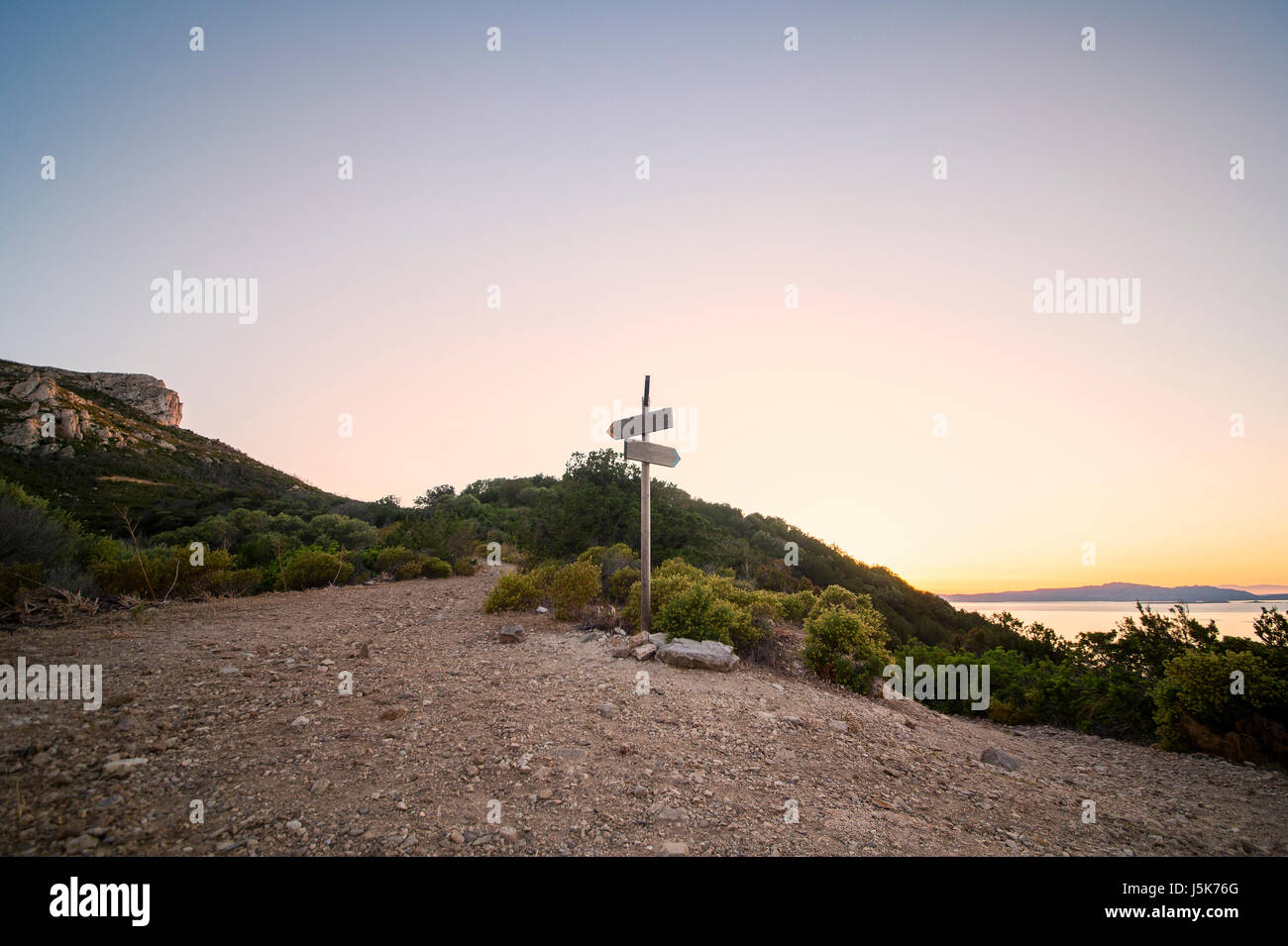 Rural scenic landscape with crossroad on hill in forest at sunset. Two different directions. Concept of choose the - Stock Image