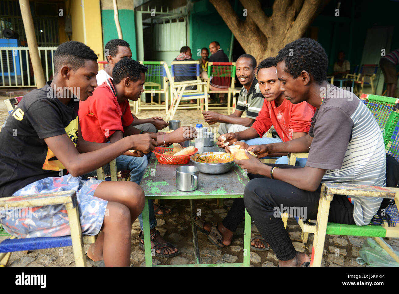 Local Tigrayans enjoying a traditional breakfast of foul with veggies and bread. - Stock Image
