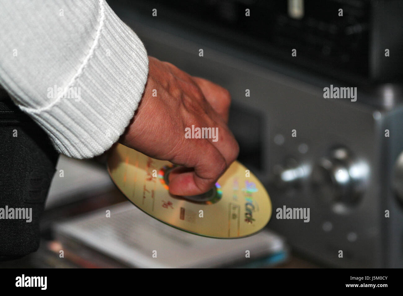 hand finger music listen disc party celebration sweater hold serve grasp CD Stock Photo