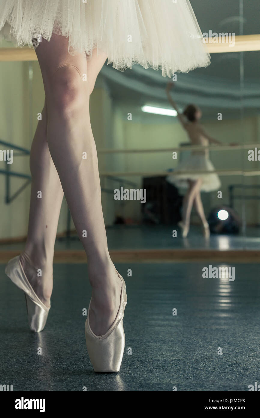 Ballerina in pointes and a pack warms up before the dance lesson. Crossed long slender female feet. Classical ballet. - Stock Image