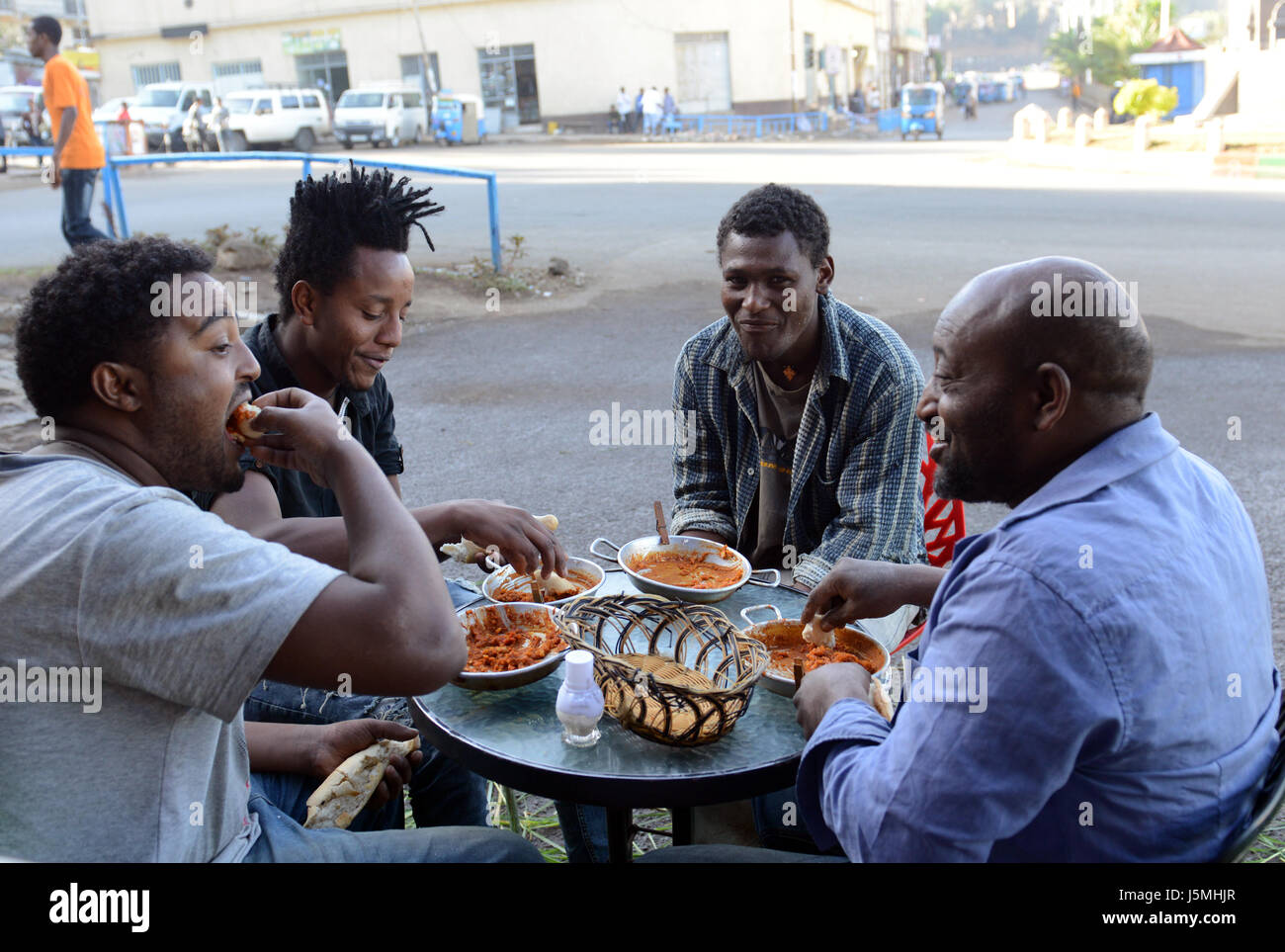 Ethiopian friends enjoying a Foul meal in the center of Gondar, Ethiopia. - Stock Image