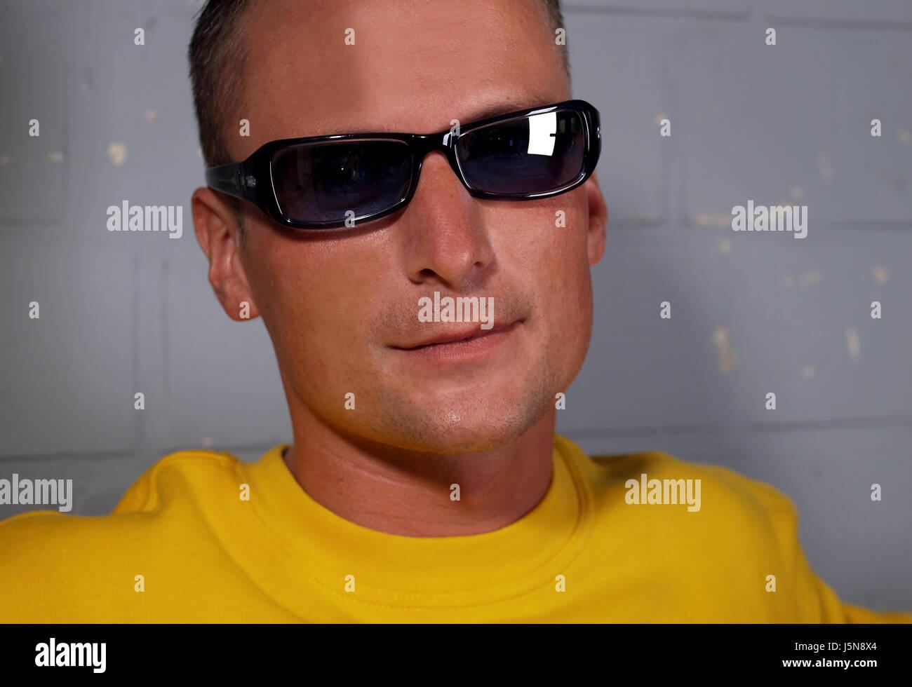 poses,wall,sweater,sunglasses,sunglass,yellow,man,pose,lichtreflex - Stock Image