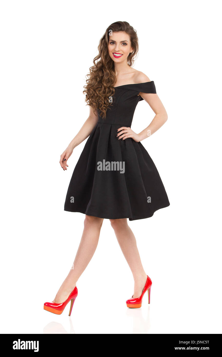 40d4f66f5803 Beautiful young woman in elegant black cocktail dress and red high heels is  walking