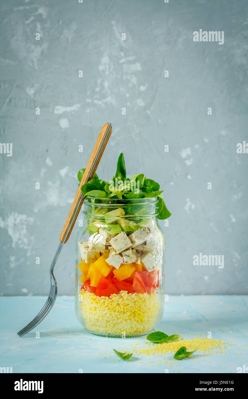 Vegan salad with couscous, tofu and vegetables in a jar. Love for a healthy vegan food concept Stock Photo