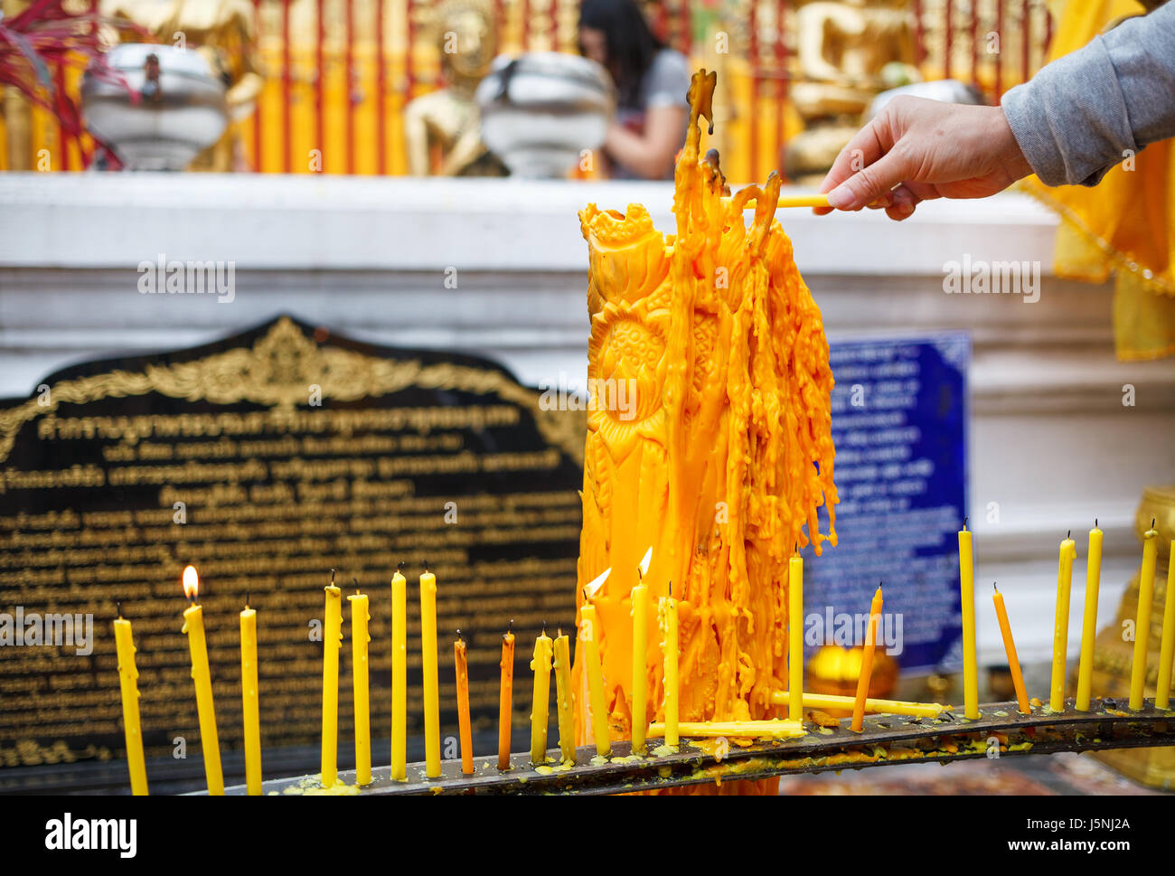 Hand with candle in Wat Doi Suthep Buddhist Temple in Ciang Mai, Thailand - Stock Image