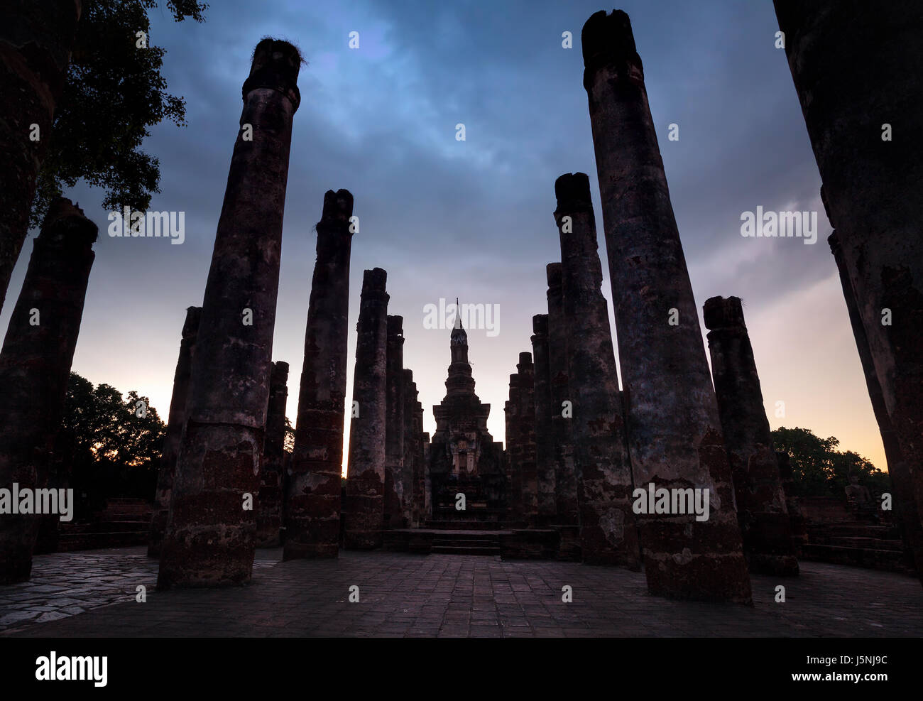 Ancient ruined column of Temple in Sukhothai at overcast sunset sky, Thailand - Stock Image