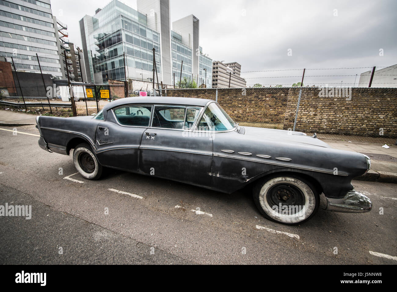 Aging 1950s (1956 ?) Buick Super Riviera in a London side street. With whitewall tyres / tires. Decay. Space for - Stock Image