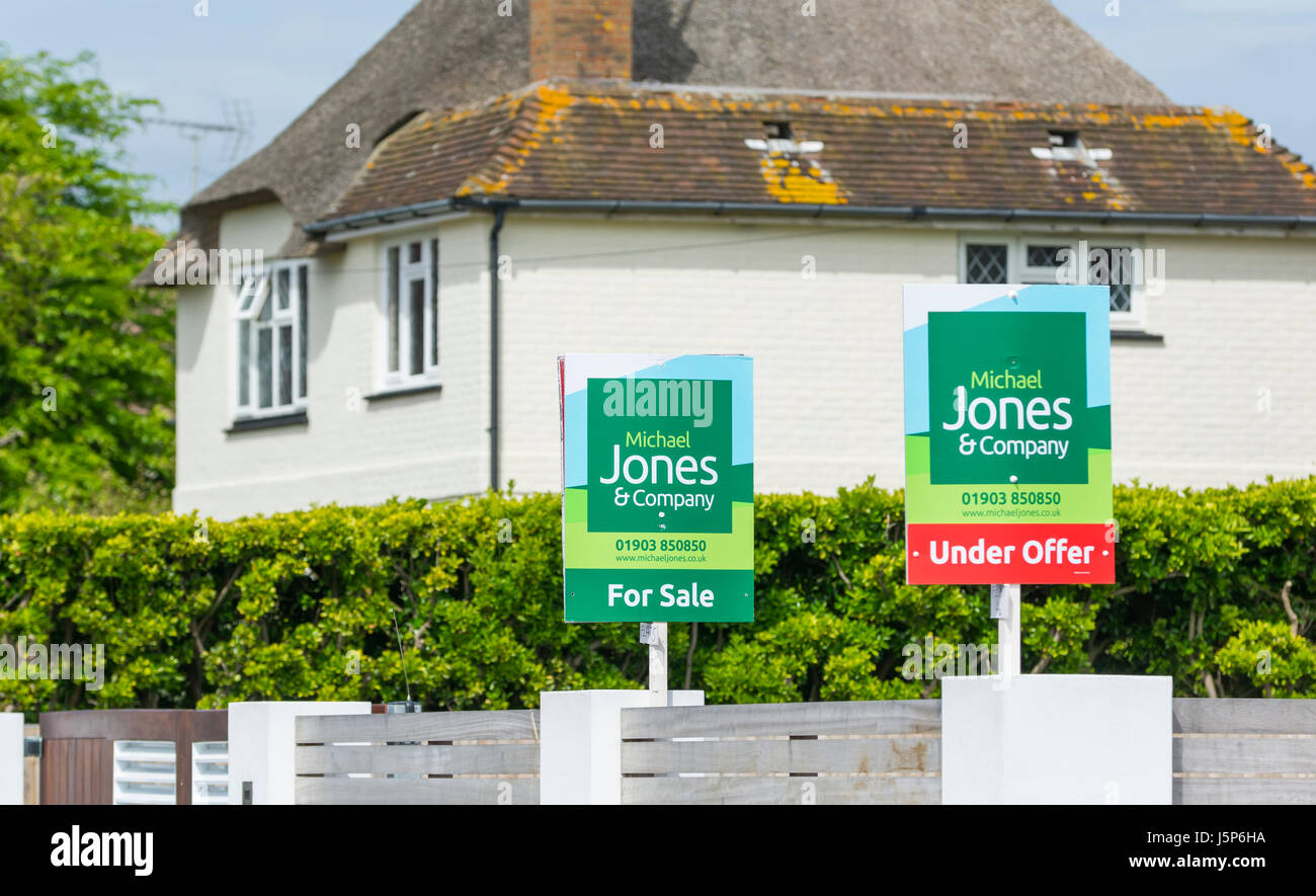 Under Offer sign and For Sale sign outside houses in the UK. Stock Photo