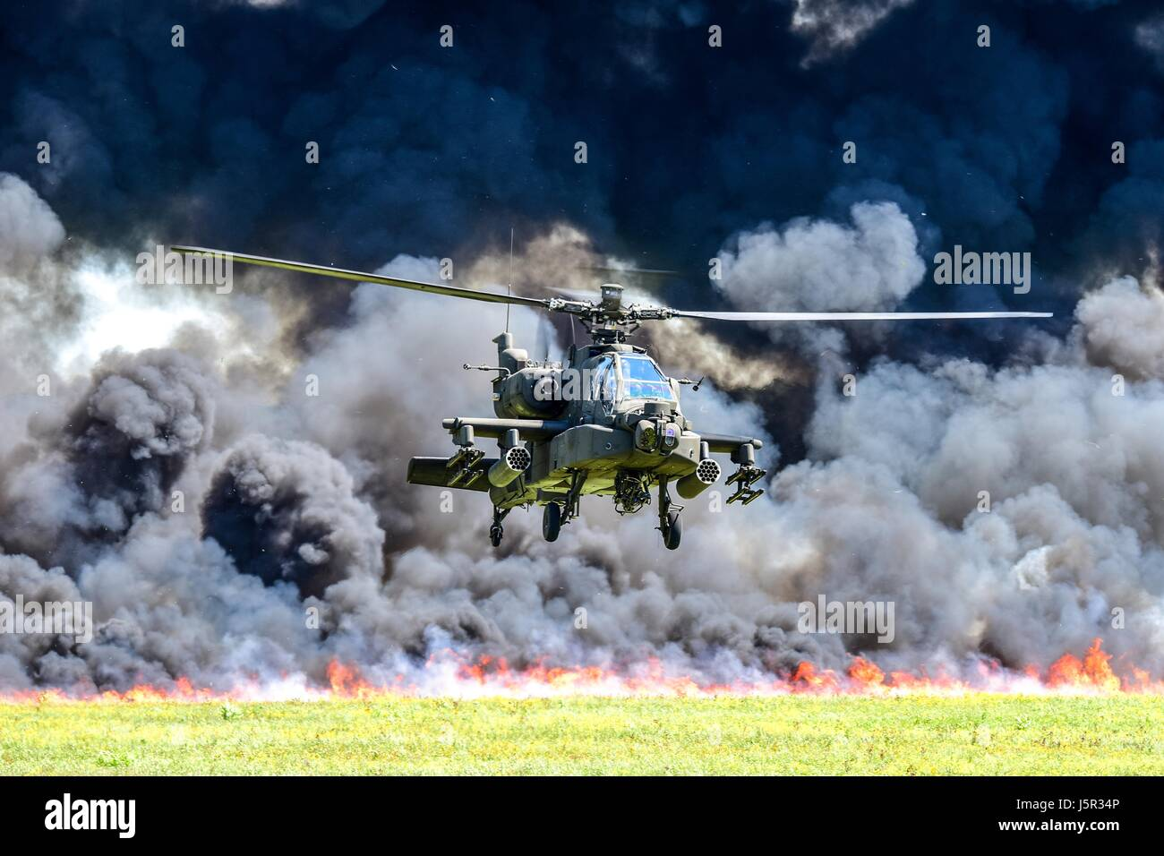 A U.S. Army AH-64D Apache attack helicopter flies in front of a wall of fire during the South Carolina National Stock Photo